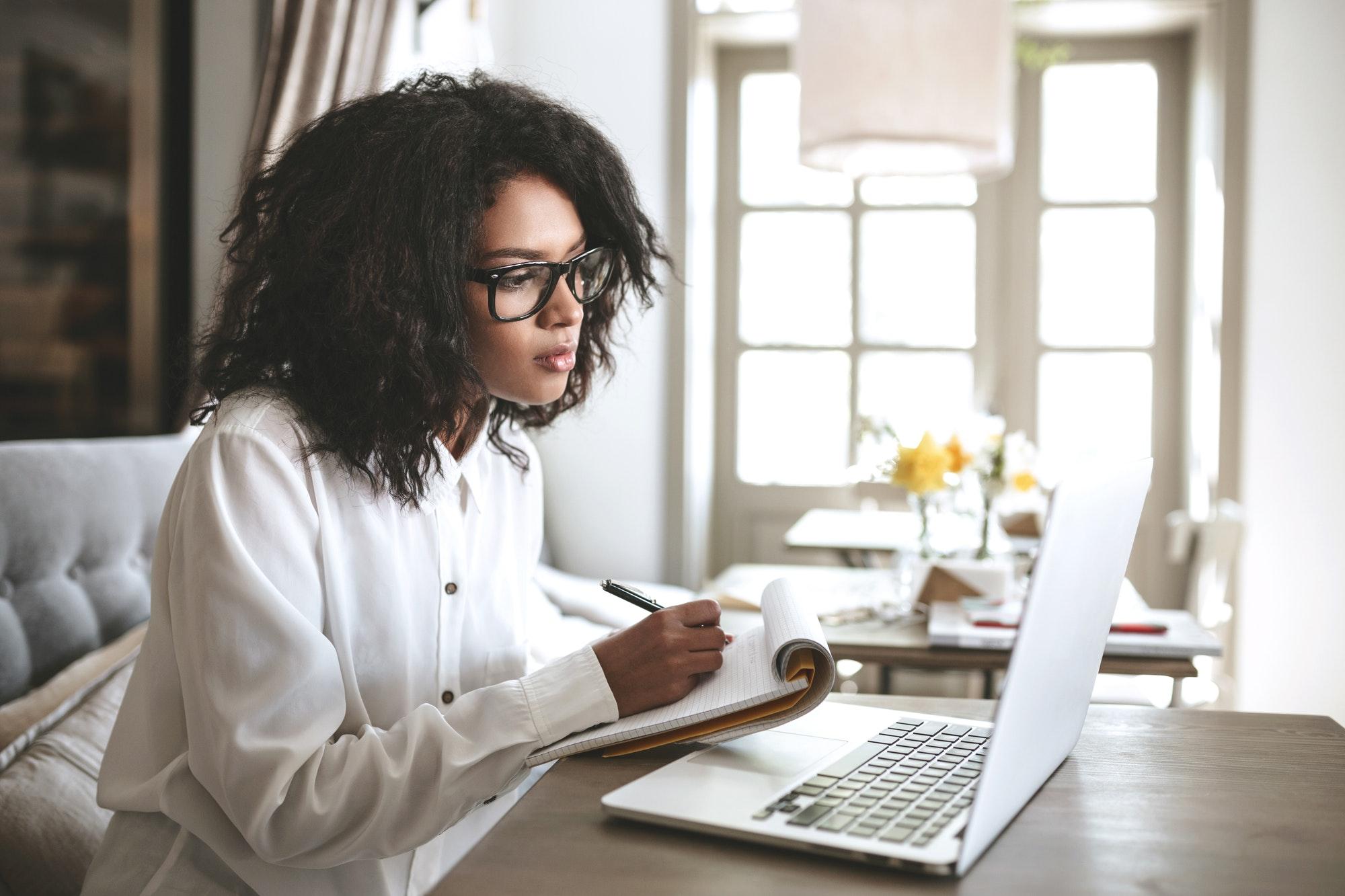 Frau sitzt vor Laptop und schreibt sich Notizen auf